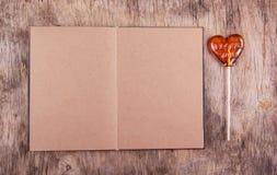 打开与空白页和棒棒糖的食谱书以心脏的形式 开放的日志 库存照片