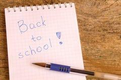 打开与题字的白色笔记薄回到有氦气笔的学校在木桌上 免版税库存图片