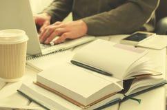 打开与黑笔的笔记薄在工作台 纸咖啡、办公室材料、膝上型计算机和工人背景的 免版税库存照片