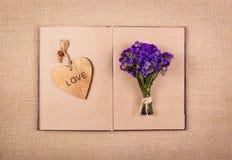 打开书、心脏书签和花 浪漫概念 库存照片