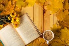 打开书、菊花花束和咖啡,在与叶子的木桌上 免版税图库摄影
