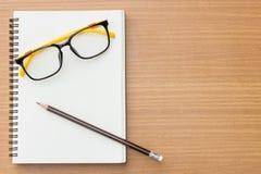 打开书、玻璃和铅笔在织地不很细木头 免版税库存图片