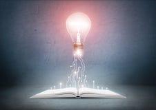 打开书和发光的电灯泡在它 知识,教育概念 免版税库存图片
