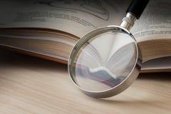 打开书和放大镜 免版税库存图片