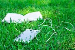 打开书和白色智能手机有说谎在绿草,现代技术的耳机的,学会教育 库存照片