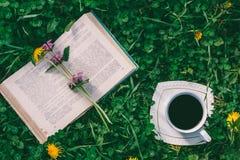打开书,咖啡在一个茶碟的在与一棵绿色三叶草的清洁 图库摄影