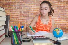 打开书,在木桌上的精装书五颜六色的书 在家坐在书桌的女孩,做家庭作业 库存图片