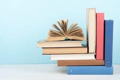 打开书,在木桌,蓝色背景上的精装书五颜六色的书 回到学校 复制文本的空间 教育 库存照片