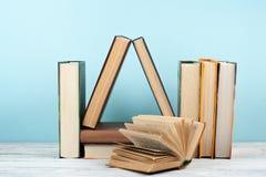 打开书,在木桌,蓝色背景上的精装书五颜六色的书 回到学校 复制文本的空间 教育 图库摄影