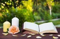 打开书,蜡烛,并且芬芳上升了 浪漫概念 与空的页的一本书在桌上 复制空间 免版税库存照片