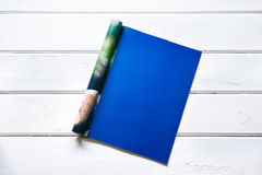 打开了杂志页的空的深蓝嘲笑在白色woode 库存图片