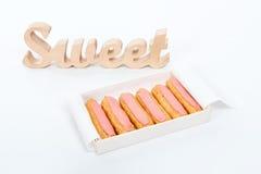打开交付纸箱用六块新鲜的桃红色杯形蛋糕和木词甜点在白色背景 浪漫礼品 不健康 库存图片