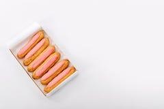 打开交付纸箱用在白色背景的六块新鲜的桃红色杯形蛋糕 顶视图,文本的空间 不健康或节食 库存照片