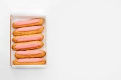 打开交付纸箱用在白色背景的六块新鲜的桃红色杯形蛋糕 顶视图,文本的空间 不健康或节食 免版税库存图片