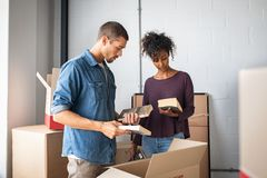 打开从纸板箱的年轻夫妇书 免版税库存图片