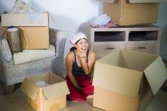 打开从纸板箱移动的年轻美丽和愉快的亚裔中国妇女激动的在家客厅地板财产 库存图片