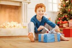 打开他的圣诞节礼物的放光的红头发人男孩 库存图片