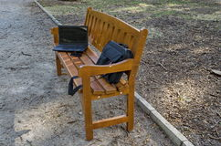 打开便携式计算机、袋子和电话在长木凳 库存图片
