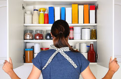 打开充分的餐具室的妇女 免版税库存图片