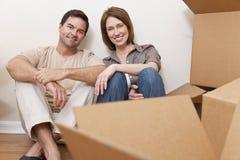 打开包装盒的愉快的夫妇移动之家 免版税图库摄影