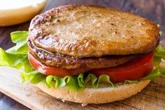 打开双重汉堡用土耳其肉、莴苣和蕃茄木表面上 库存照片