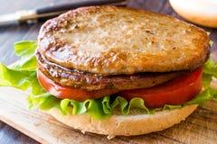 打开双重汉堡用土耳其肉、莴苣和蕃茄木表面上 免版税库存照片