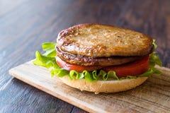打开双重汉堡用土耳其肉、莴苣和蕃茄木表面上 免版税库存图片