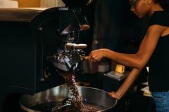 打开咖啡烘烤器的年轻barista 免版税库存照片