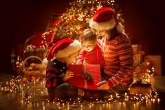 打开圣诞节的家庭点燃当前礼物盒在Xmas树、愉快的母亲和孩子下 免版税图库摄影