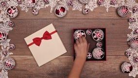 打开圣诞节礼物显露的束钩针编织的xmas中看不中用的物品的手 股票录像