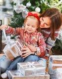 打开圣诞节礼物的两个愉快的姐妹 免版税库存照片