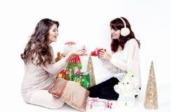 打开圣诞节礼物的两名微笑的妇女 免版税库存图片