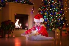 打开圣诞节礼物的孩子在壁炉 免版税图库摄影