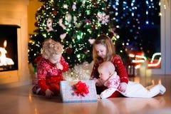 打开圣诞节礼物的孩子在壁炉 库存图片
