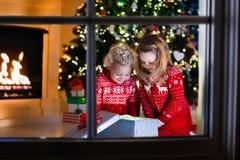 打开圣诞节礼物的孩子在壁炉 库存照片
