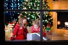 打开圣诞节礼物的孩子在壁炉 免版税库存图片