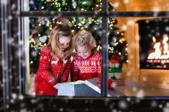 打开圣诞节礼物的孩子在壁炉 免版税库存照片