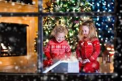 打开圣诞节礼物的孩子在壁炉 图库摄影