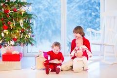 打开圣诞节礼物的孩子 免版税库存图片