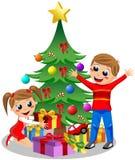 打开圣诞节礼物的逗人喜爱的孩子 图库摄影