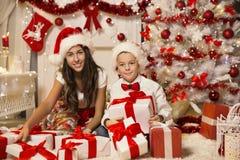 打开圣诞节礼物礼物盒的孩子,庆祝孩子 免版税库存图片