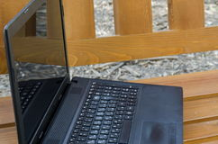 打开在一个长木凳的便携式计算机 免版税库存图片