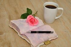 打开在一张木桌上的日志与桃红色上升了,笔和杯子 免版税库存图片