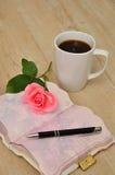 打开在一张木桌上的日志与桃红色上升了,笔和杯子 库存图片