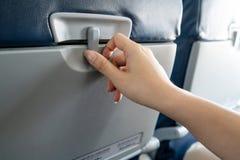 打开在位子前面的一个盘子的亚洲女性乘客尝试的手在低成本飞机由幻灯片为infli开锁和准备 免版税库存图片