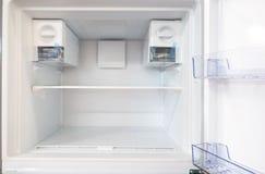 打开在冰箱里面的空的新的白色冰箱有架子的 免版税库存图片