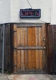 打开在土气木门上的标志 免版税库存照片