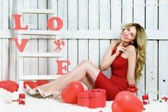 打开在心脏的形状的女孩一个红色礼物盒 免版税库存图片