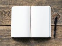 打开在春天有白皮书的笔记的和图画的笔记本与铅笔 背景困厄的木头, 库存图片