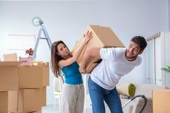 打开在有箱子的新房的年轻家庭 免版税库存图片